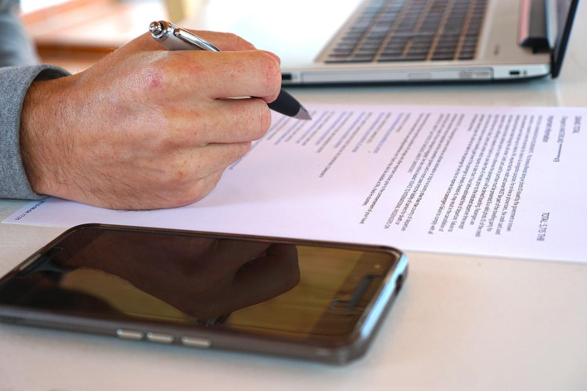 A man reviewing a contract; near laptop and smartphone