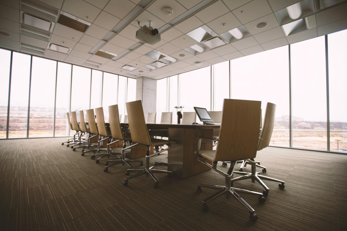 A conference room in a high rise building with wall to wall windows