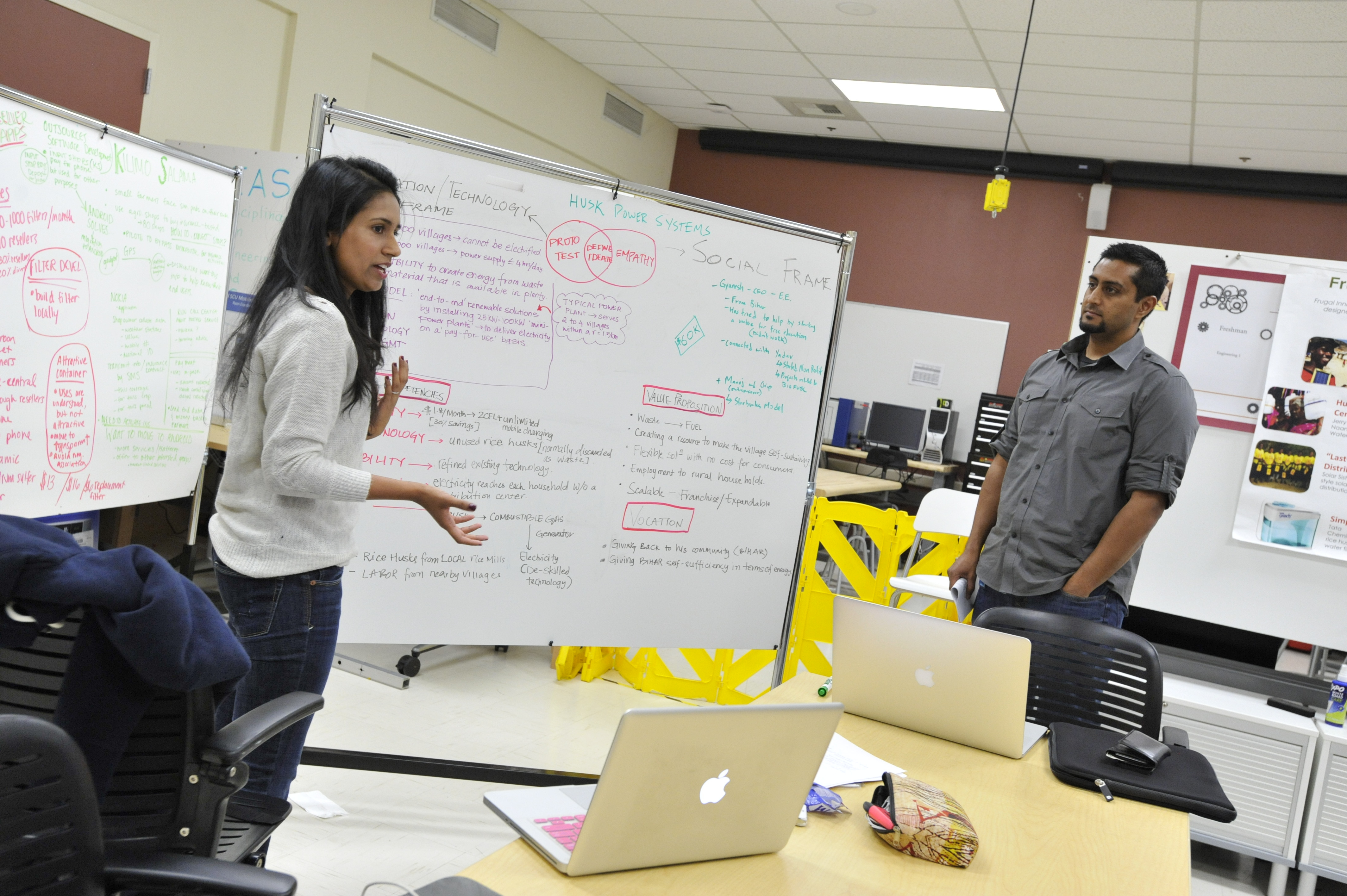 Two students stand in front of a white board with brainstorming work on it, presenting to colleagues.
