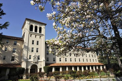 An exterior image of Nobili Hall with flower blossoms.