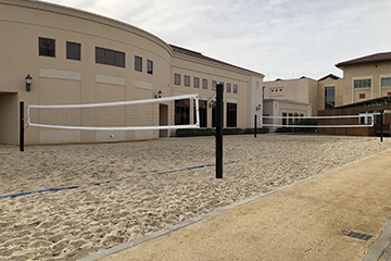 image of sand volleyball court behind malley