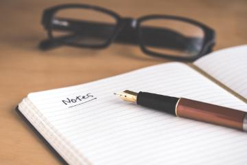 Fountain pen with lined notebook and glasses. Photo by David Travis, Unsplash.