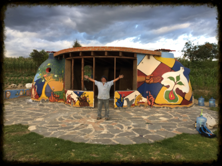 Arturo standing in front of colored building, Cholula Immersion 2016 image link to story