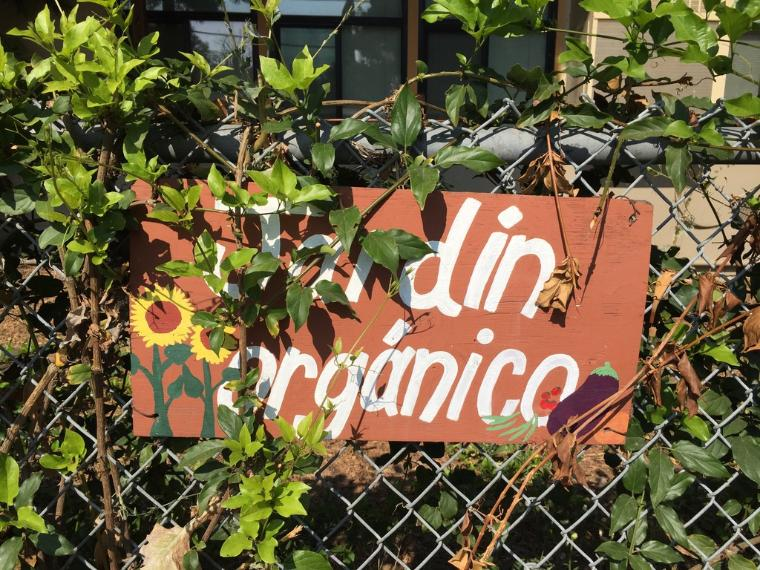 Jardin Organico sign on a metal fence, partially covered by greenery
