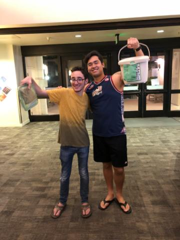 2 SCU students hold up their personal compost pails in the residence halls