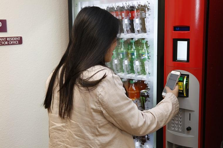 Woman using her digital ACCESS card to make a vending machine purchase. image link to story