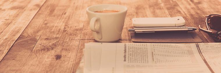 Newspaper next to phone and cup of coffee