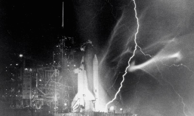 Lightning striking the ground at the base of a space ship, poised to launch