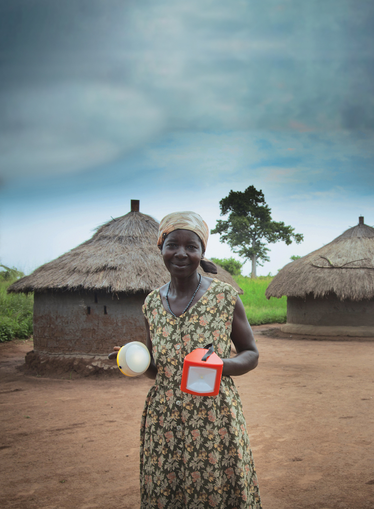 African woman holding two solar powered lamps