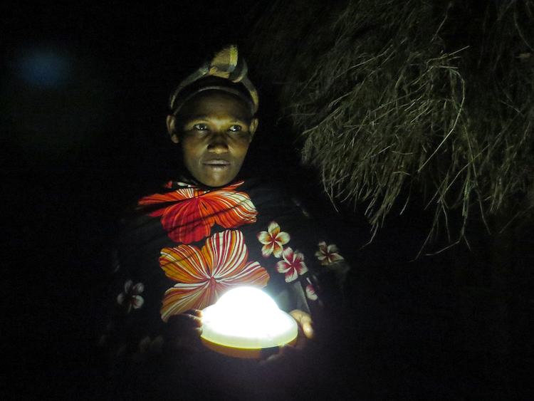 A Tanzanian woman holding a solar light outside in the dark