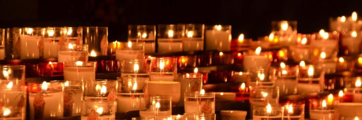 Photograph of votive candles lit inside a church