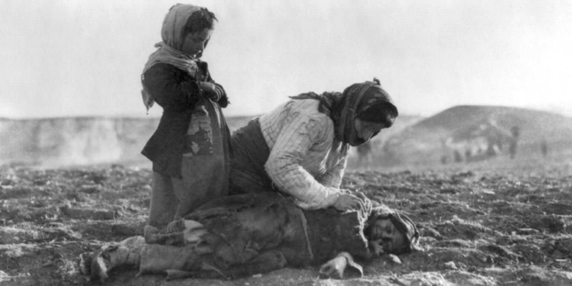 Historic photo of Armenian woman kneeling in a battllefield with two daughters.
