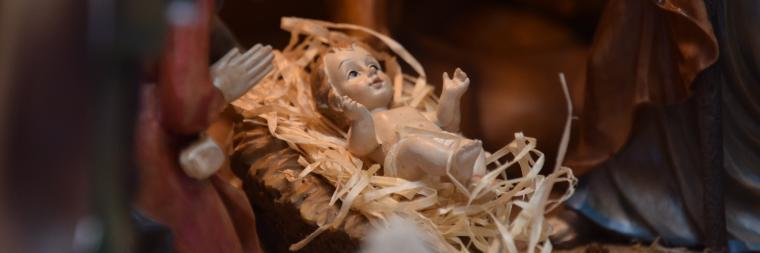 Close up of baby Jesus in a small nativity manger