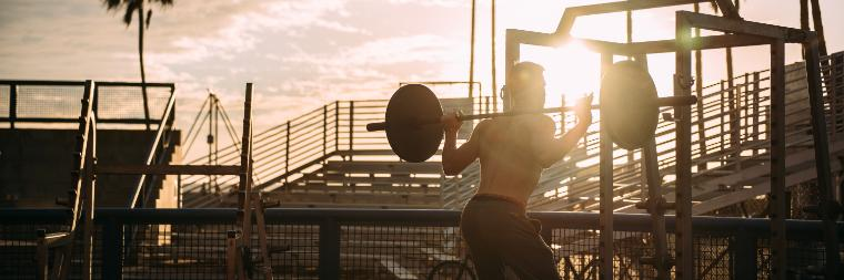 Man lifting weights at an outdoor beach-side gym at sunset