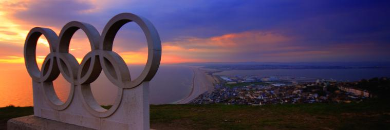 A statue of the Olympic rings on a hill above a coastal city at sunset