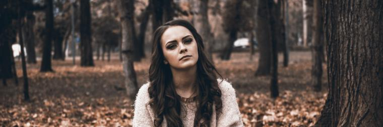 Woman sitting in the forest looking annoyed