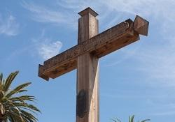 Wooden cross in front of a blue sky.