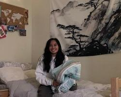 Young woman sitting on a bed in her residence hall room.