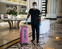 A masked hotel worker standing next to a suitcase.
