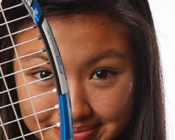 Young woman smiling behind a tennis racket.