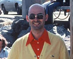 Portrait of a man in sunglasses wearing an orange shirt and a yellow sweater.