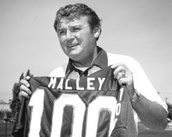 Black and white photo of Pat Malley holding jersey number 100.