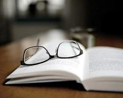 A pair of glasses lying on an open book.