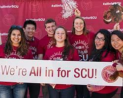 Students holding All in for SCU banner.