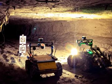Two autonomous robots illuminate a target found in a mining tunnel image link to story