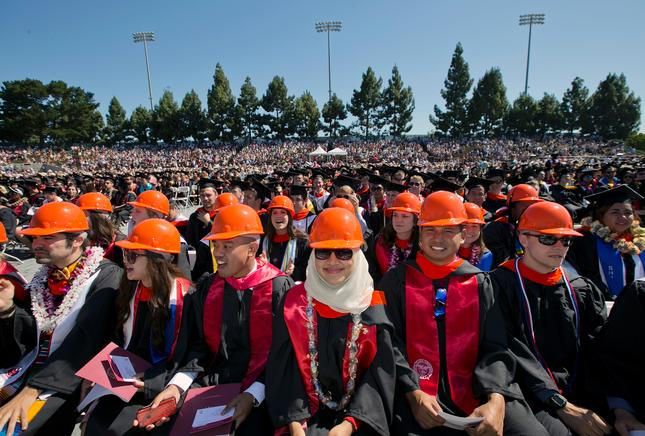 Civil engineering students wear orange hard hats with their gowns instead of caps at undergraduate commencement