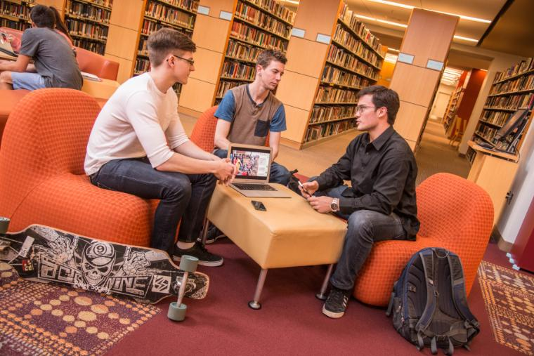 Computer engineering seniors Michael Brew and Bryant Larsen work on an Uber-like mobile app for Uganda with economics major and Fulbright Fellow Tyler Van Herweg in the SCU library. image link to story