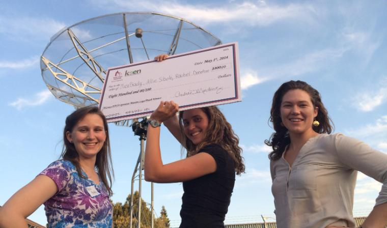 Three female students show off their big check as winners of the SporeSat Challenge