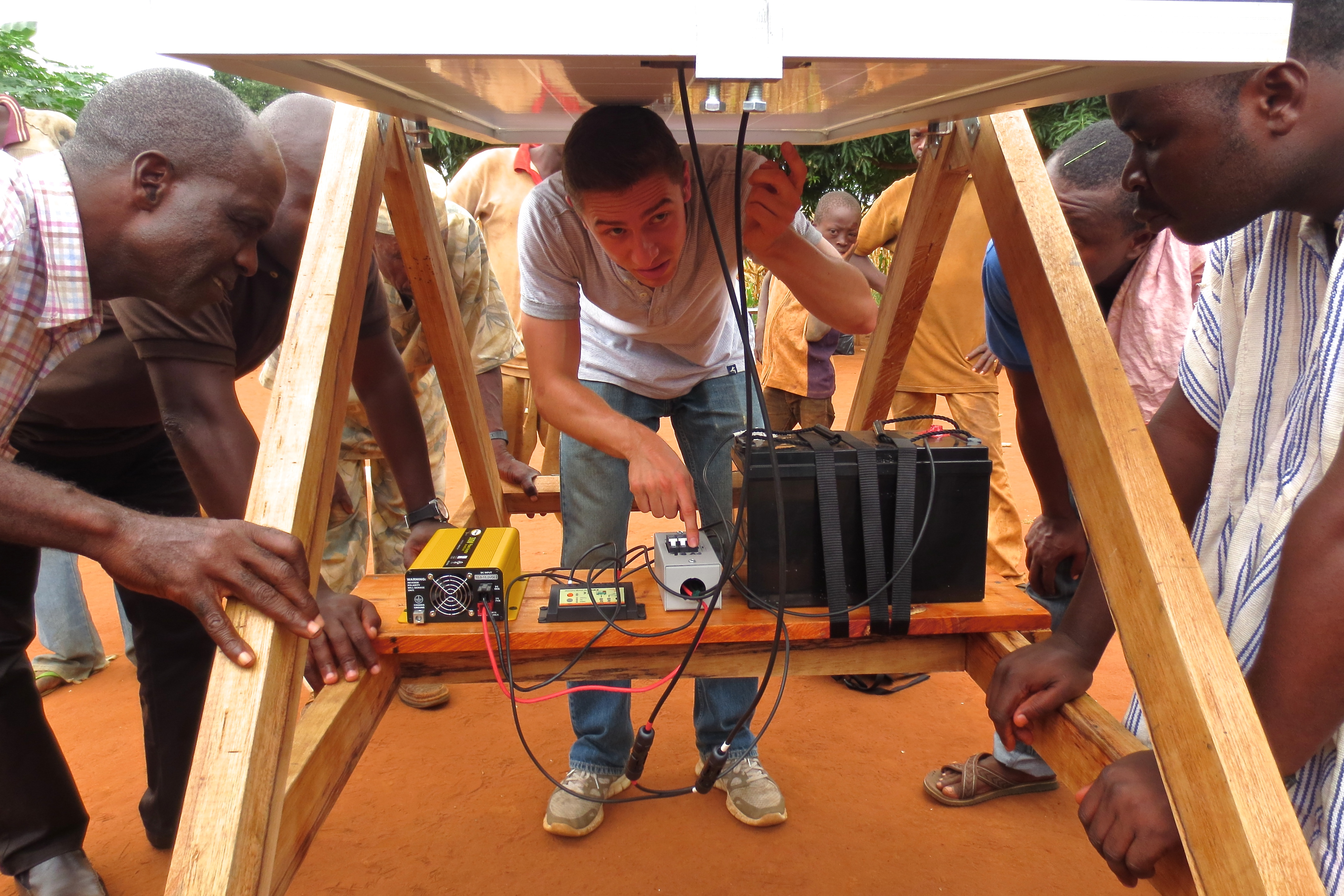 David Lyons' 16 flips the switch on his solar-powered charging station in Ghana. image link to story