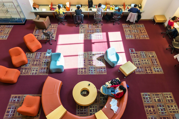 Students studying on the library's colorful lower level